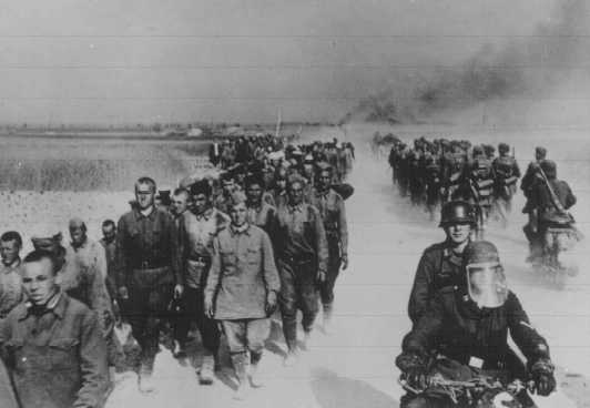 At left, a column of Soviet prisoners of war, under German guard, marches away from the front. Place uncertain, July 1, 1941.