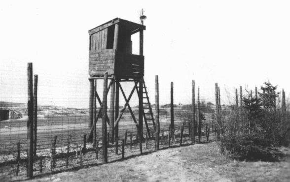 A view of one of the watchtowers and part of the perimeter fence at Orhdruf, part of the Buchenwald camp system, seen here after US forces liberated the camp. Ohrdruf, Germany, April 1945.