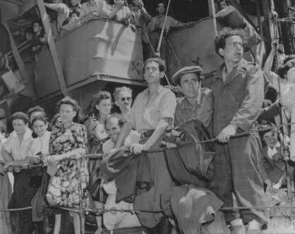 "Refugees crowd the rail of the Aliyah Bet (""illegal"" immigration) ship ""Josiah Wedgwood,"" anchored at the Haifa port. British soldiers transported the passengers to the Atlit internment center. Palestine, June 27, 1946."