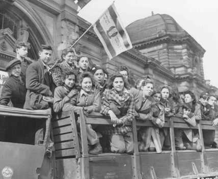 Jewish refugee children gather in the US zone of occupation in Germany, en route to Palestine. One refugee waves a Zionist flag. Frankfurt, Germany, April 10, 1946.