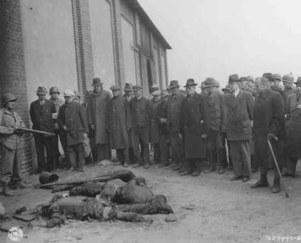 An American soldier stands guard as mayors and citizens of local towns view the corpses of inmates of the Rottleberode subcamp, who were killed when the SS locked them in a barn and set it on fire. Gardelegen, Germany, April 18, 1945.