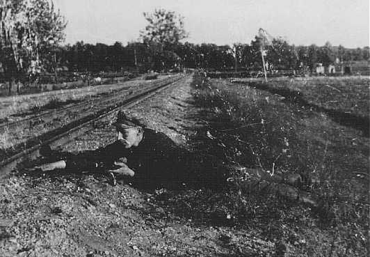 Jewish partisan Boris Yochai plants dynamite on a railroad track. Vilna, 1943 or 1944.