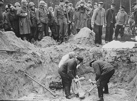 American troops with the 82nd Airborne Division look on as German exhume corpses from a mass grave. Wöbbelin, Germany, May 6, 1945.