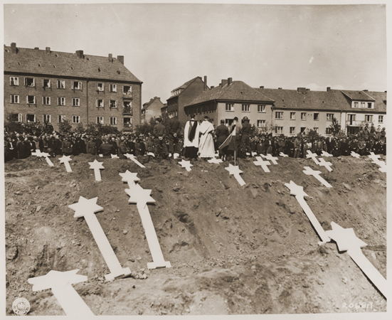 Under orders from officers of the US 8th Infantry division, German civilians from Schwerin attend funeral services for 80 prisoners killed at the Wöbbelin concentration camp. The townspeople were ordered to bury the prisoners' corpses in the town square. Germany, May 8, 1945.