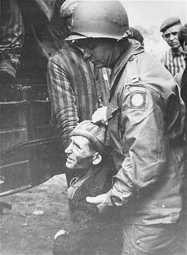 A chaplain with the 82nd Airborne Division helps a survivor board a truck that will evacuate him from the Wöbbelin concentration camp to an American field hospital. Germany, May 4, 1945.