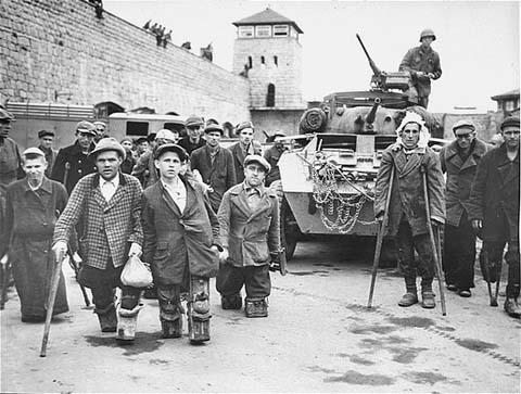Des détenus polonais et soviétiques handicapés face à un tank de la 11ème division blindée, Troisième Armée américaine. Cette photo a été prise au camp de concentration de Mauthausen immédiatement après la libération. Autriche, du 5 au 7 mai 1945.