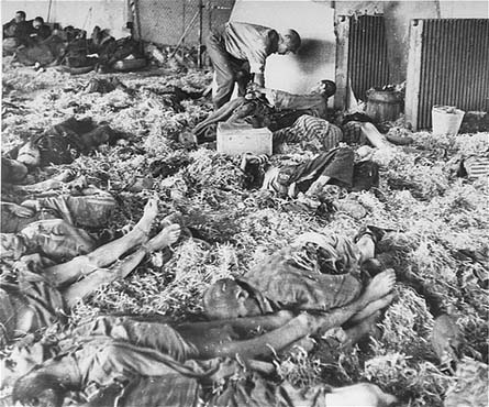 An American soldier tends to a former prisoner lying among corpses of victims at the Dora-Mittelbau concentration camp, near Nordhausen. Germany, after April 10, 1945.