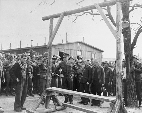 """During an official tour of the newly liberated Ohrdruf concentration camp, an Austrian Jewish survivor describes to General Dwight Eisenhower and the members of his entourage the use of the gallows in the camp. Among those pictured is Jules Grad, correspondent for the US Army newspaper """"Stars and Stripes"""" (on the right). Ohrdruf, Germany, April 12, 1945."""