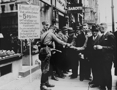 SA men distribute leaflets during the anti-Jewish boycott. Berlin, Germany, 1933.