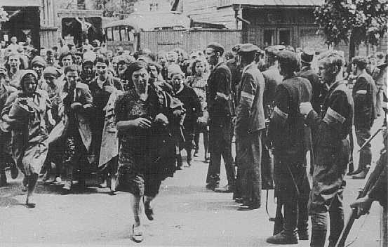 Lithuanian militiamen in Kovno round up Jews during an early pogrom. Kovno, Lithuania, June 25-July 8, 1941.