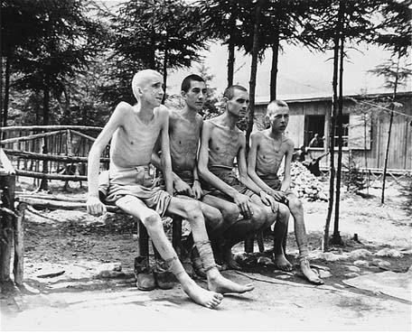 Four emaciated survivors sit outside in the newly liberated Ebensee concentration camp. Photograph taken by Signal Corps photographer J Malan Heslop. Ebensee, Austria, May 8, 1945.