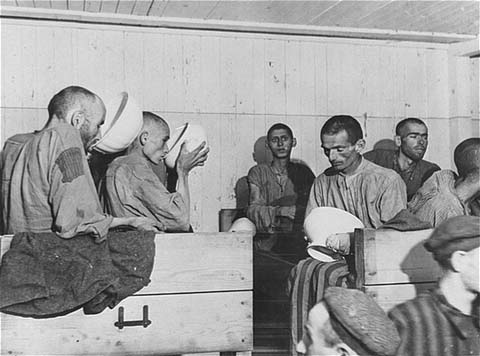 Liberated prisoners at the Ebensee camp. Too weak to eat solid food, they drink a thin soup prepared for them by the US Army. Photograph taken by Signal Corps photographer J Malan Heslop. Austria, May 8, 1945.