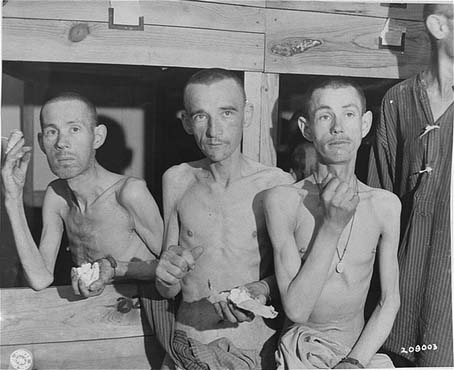 Emaciated survivors in the Ebensee subcamp of the Mauthausen concentration camp suck on sugar cubes provided by American soldiers upon the liberation of the camp. Photograph taken by Signal Corps photographer J Malan Heslop. Ebensee, Austria, May 8, 1945.