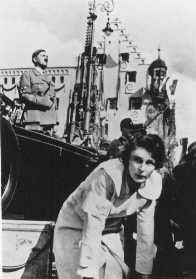 "Leni Riefenstahl, with Adolf Hitler in the background, directs the shooting of a film about the Reich Party Day. Here she is shooting a segment called ""Day of the Reich Work Service."" Nuremberg, Germany, 1936."