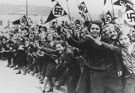 Members of the League of German Girls wave Nazi flags in support of the German annexation of Austria. Vienna, Austria, March 1938.