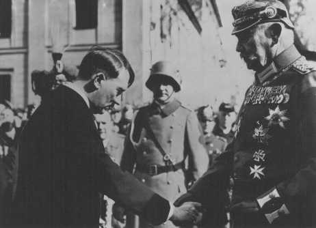 Recently appointed as German chancellor, Adolf Hitler greets President Paul von Hindenburg in Potsdam, Germany, on March 21, 1933. This pose was designed to project an image of Hitler as non-threatening to the established order. This particular image is from a popular postcard. The photo also appeared widely in both the German and international press. Hitler appears in civilian dress, bowing in deference to the heavily decorated von Hindenburg. The March 5, 1933, elections had conferred legitimacy on Hitler's leadership.