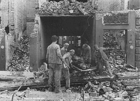 Concentration camp prisoners, many from satellite camps of Neuengamme, remove corpses of German civilians after Allied bombings of Hamburg. Germany, August 1943.