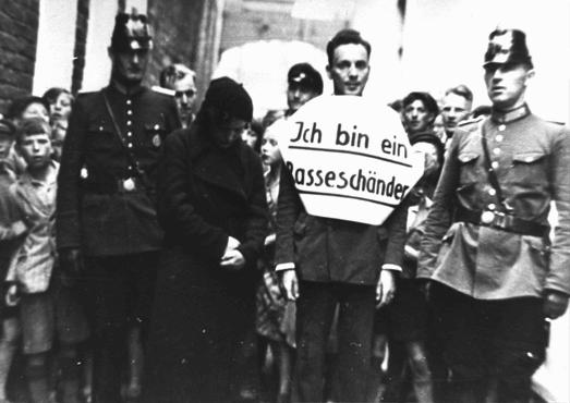 "Public humiliation: ""I am a defiler of the race."" In this photograph, a young man who allegedly had illicit relations with a Jewish woman is marched through the streets for public humiliation. Flanked by German police officers, he wears a sign that reads, ""I am a defiler of the race."" These events were calculated to both punish the so-called offenders and to make a public example of them as a deterrent to others who might not fully subscribe to Nazi racial theory. Norden, Germany, July 1935."