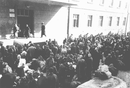 """Jews outside the """"Monopol"""" tobacco factory, used as a transit camp by Bulgarian authorities during deportations from Macedonia to the Treblinka camp in German-occupied Poland. Skopje, Yugoslavia, March 1943."""