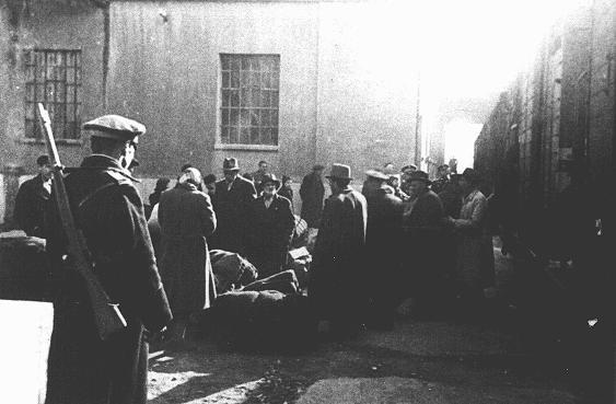 """Juifs de Macédoine et de Thrace sous occupation bulgare lors de la déportation de la manufacture de tabac """"Monopol"""" (utilisée en tant que camp de transit) vers Lom. Ils furent envoyés à Vienne et ensuite au camp de Treblinka. Skopje, Yougoslavie, du 11 au 31 mars 1943."""