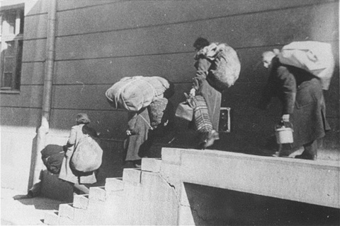 A family of Macedonian Jews carries their luggage down a flight of stairs as they leave the Tobacco Monopoly transit camp for the deportation trains. Skopje, Yugoslavia, March 1943.