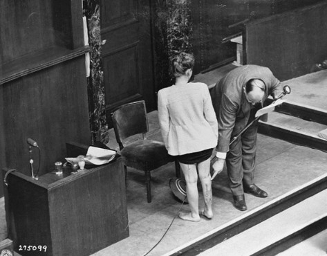 Concentration camp survivor Jadwiga Dzido shows her scarred leg to the Nuremberg court, while an expert medical witness explains the nature of the procedures inflicted on her in the Ravensbrück concentration camp on November 22, 1942. The experiments, including injections of highly potent bacteria, were performed by defendants Herta Oberheuser and Fritz Ernst Fischer. December 20, 1946.