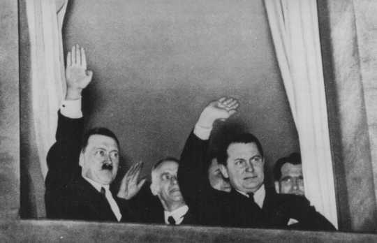 Adolf Hitler, Wilhelm Frick, and Hermann Goering wave to a torchlight parade in honor of Hitler's appointment as chancellor. Behind Goering stands Rudolf Hess. Berlin, Germany, January 30, 1933.