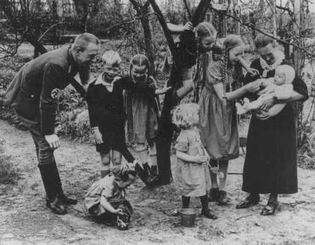 "Nazi policy encouraged racially ""acceptable"" couples to have as many children as possible. Because of the number of children in this Nazi party official's family, the mother earned the ""Mother's Cross."" Germany, date uncertain."