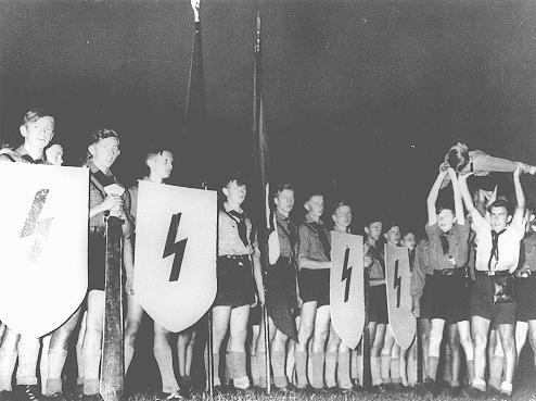 "A Hitler Youth ceremony of the sort conceived by Baldur von Schirach—to strengthen dedication to Hitler—in which members recited verses, sang patriotic songs, and performed ""mock funerals"" for ""fallen comrades."" Germany, date uncertain."