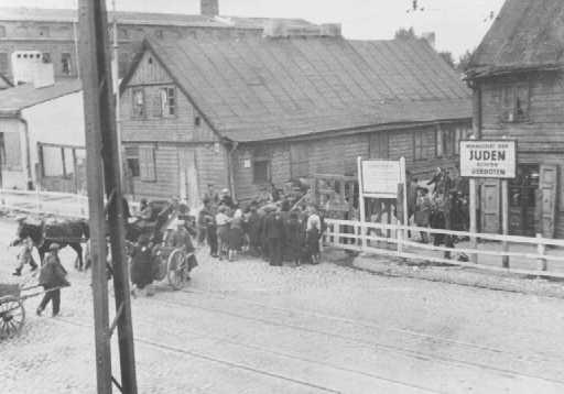 """L'une des entrées du ghetto. La pancarte dit """"Zone de résidence pour Juifs - entrée interdite."""" Ghetto de Lodz, Pologne, 1941."""