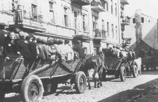 "Jews, mostly children, proceed on horse-drawn wagons to assembly points for deportation. They are guarded by the Jewish police. Lodz ghetto, Poland, during the ""Gehsperre"" Aktion, September 5-12, 1942."