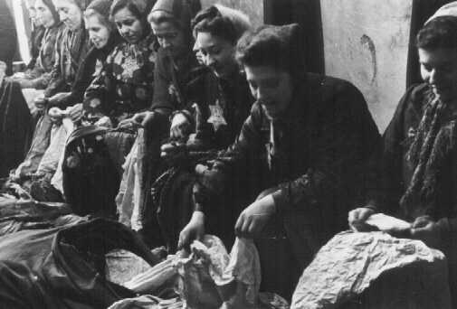 Jewish women who were seized for forced labor sort expropriated cloth. Lodz ghetto, Poland, date uncertain.