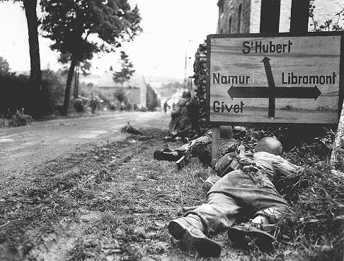 American soldiers of the 8th Infantry Regiment seek cover behind hedges and signs to return fire to German forces holding the town of Libin. Belgium, September 7, 1944.