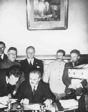 Le ministre soviétique des Affaires étrangères Viacheslav Molotov signe le pacte germano-soviétique tandis que le dirigeant soviétique Joseph Staline (en uniforme blanc) et le ministre allemand des Affaires étrangères Joachim von Ribbentrop (derrière Molotov) regarde. Moscou, Union soviétique, 23 août 1939.