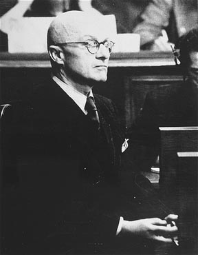 "Defendant Gregor Ebner testifies at the RuSHA Trial. A physician by training, Ebner oversaw a Lebensborn program to produce children from ""racially superior"" Aryan parents and identify such children in occupied territories. He was acquitted of crimes against humanity and war crimes. Ebner was convicted of membership in a criminal organization, but released with time served. He died in 1974."