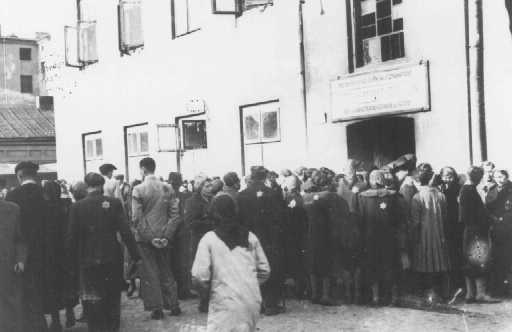 Jews in the Lodz ghetto line up outside the labor office of the Jewish council in the hopes of finding employment outside the ghetto. Lodz, Poland, between 1941 and 1943.