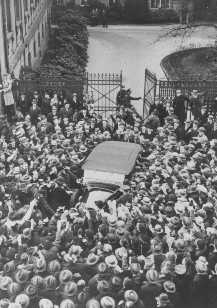 A crowd cheers Adolf Hitler as his car leaves the Reich Chancellery following a meeting with President Paul von Hindenburg. Berlin, Germany, November 19, 1932.