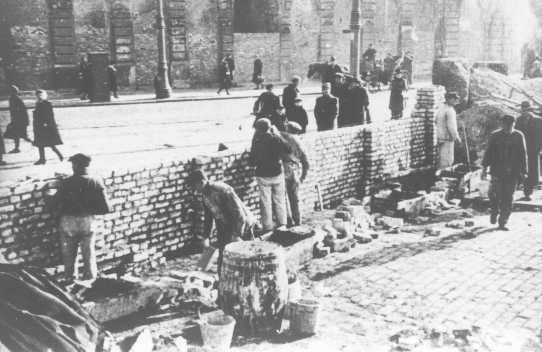 Jews work on the construction of a wall around the Warsaw ghetto area. The Germans announced the construction of a ghetto in October 1940 and closed the ghetto off from the rest of Warsaw in mid-November 1940.