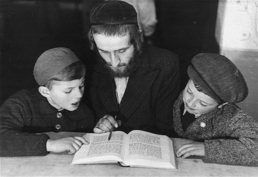 Children learn a religious text from an Orthodox Jewish teacher. Landsberg displaced persons camp, Germany, 1946-1947.