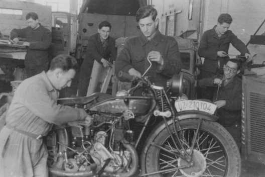 Foto de uma aula de mecânica oferecida pela instituição judaica ORT (Organização para a Reabilitação através do  Trabalho) no campo de deslocados de guerra de Landsberg. Alemanha, pós-guerra.