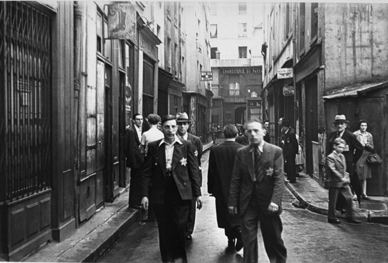 Jewish men wearing the mandatory yellow badge in the Jewish quarter of Paris. France, after June 1942.