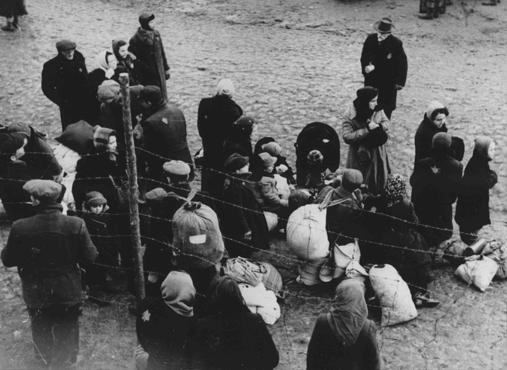 Jewish families with bundles of belongings during deportation from the Kovno ghetto to Riga in neighboring Latvia. Kovno, Lithuania, 1942.