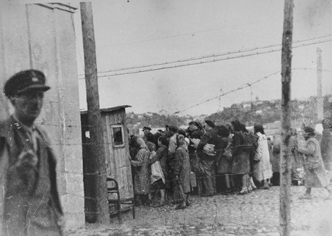 Jewish women return to the ghetto after forced labor on the outside. They line up to be searched by German and Lithuanian guards. Kovno, Lithuania, between 1941 and 1944.