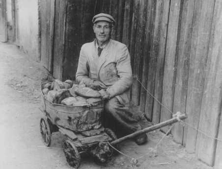 An impoverished ghetto resident sells bread on the black market. Kovno, Lithuania, between 1941 and 1943.