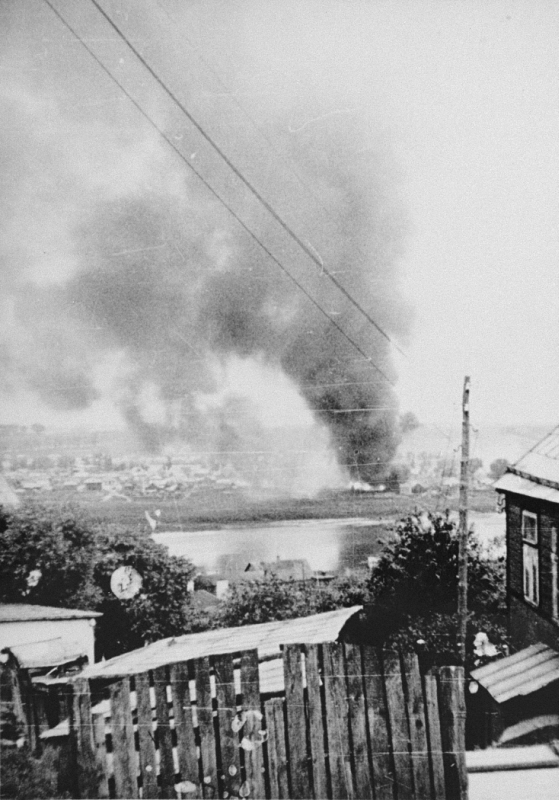 Smoke rises from buildings set ablaze in the Kovno ghetto as part of the German attempt to force Jews out of hiding during the final destruction of the ghetto. Photographed by George Kadish. Kovno, Lithuania, August 1944.