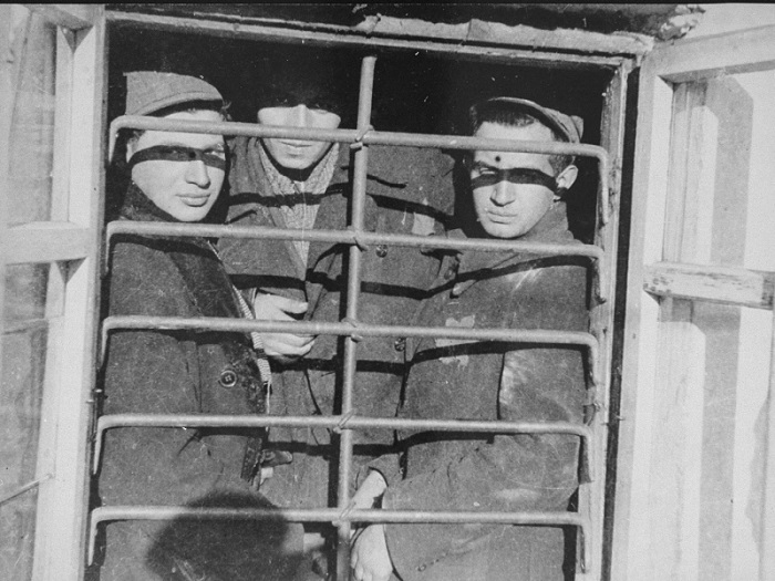 Scene photographed by George Kadish: Jewish prisoners behind a barred window in the Kovno ghetto jail. The Jewish council administered its own jail in the ghetto. Kovno, Lithuania, 1943.