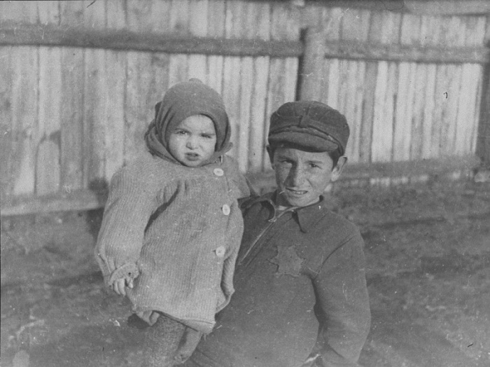 A young boy holding his younger brother in the Kovno ghetto. Older children frequently cared for younger siblings in the ghetto. Photographed by George Kadish. Kovno, Lithuania, 1941.