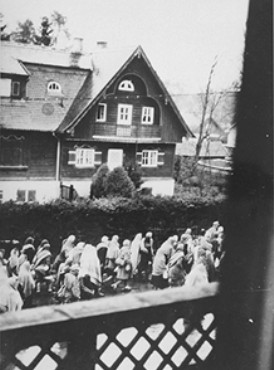 Clandestine photograph, taken by a German civilian, of Dachau concentration camp prisoners on a death march south through a village on the way to Wolfratshausen. Germany, between April 26 and 30, 1945.
