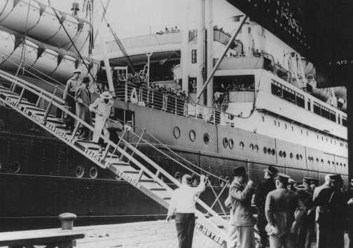 """Jewish refugees from Nazi Germany, passengers on the """"St. Louis,"""" disembark in the port of Antwerp. Cuba and the United States denied entry to these refugees. Belgian police guard the gangway. Antwerp, Belgium, June 17, 1939."""