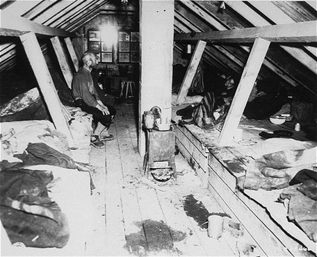 Camp forced laborers inside barracks soon after the liberation of Kaufering IV, part of a network of Dachau subcamps. Landsberg-Kaufering, Germany, 1945.